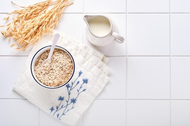 Płatki owsiane w drewnianej misce i dzbanek mleka na biały kamienny stół kuchenny. pojęcie diety wegetariańskiej. widok z góry z copyspace.