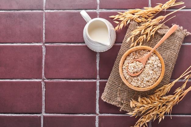 Płatki owsiane w drewnianej misce i dzbanek mleka na brązowym kamiennym stole kuchennym. pojęcie diety wegetariańskiej. widok z góry z copyspace.