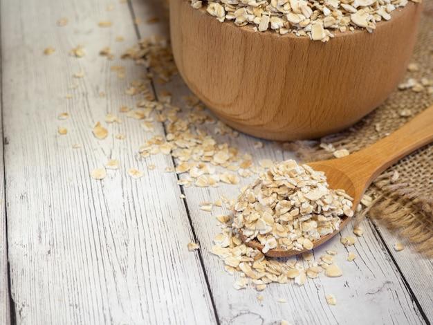 Płatki owsiane w drewnianej misce i łyżce na drewnianym stole z bliska