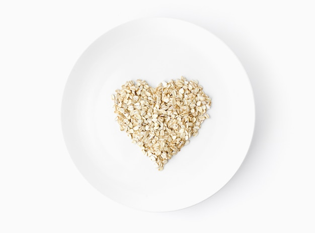 Płatki owsiane w kształcie serca strzał z góry na białej płytce na białym tle wegetariańska żywność ekologiczna. miejsce na tekst. widok z góry. leżał na płasko.
