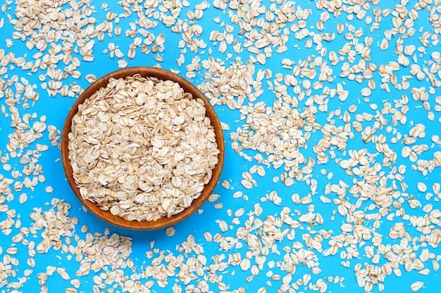 Płatki owsiane w misce na niebiesko. koncepcja zdrowej żywności