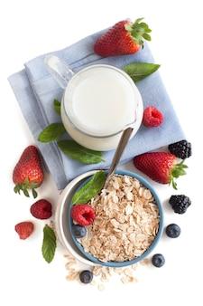 Płatki owsiane w misce z jagodami i mlekiem na białym tle na biały widok z góry