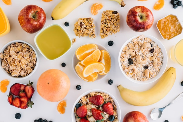 Płatki owsiane w miseczki z owocami i jagodami na białym stole