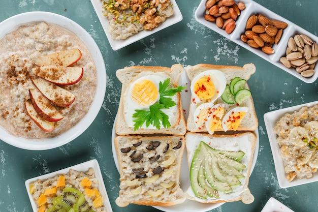 Płatki owsiane w talerzach z owocami, cynamonem, kanapkami, orzechami