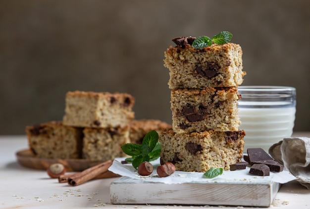 Płatki owsiane z czekoladą i filiżanką mleka. batony dietetyczne. zdrowe śniadanie lub deser.