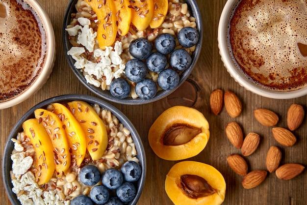 Płatki owsiane z jagodami i morelami owoce orzechy i kawa
