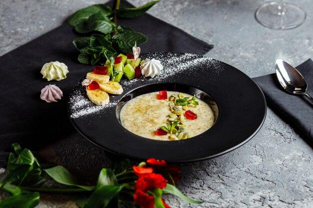 Płatki owsiane z jagodami, owocami i marmoladą na vintage turkusowy widok z góry w płaskim stylu świeckim. ciepłe i zdrowe śniadanie i żywność dietetyczna.