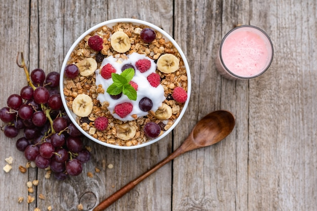 Płatki owsiane z malinami, winogronami, bananem i szklanką jogurtu na drewnianym tle.