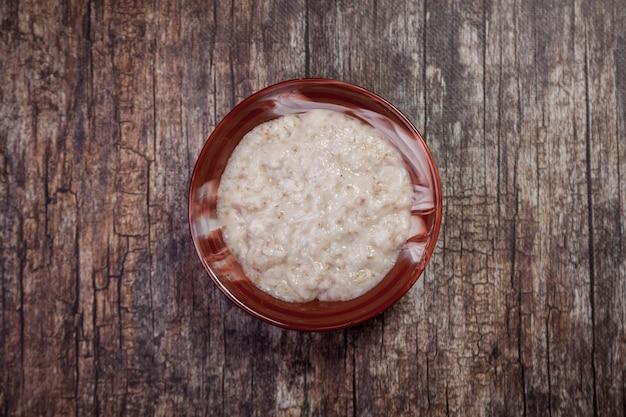 Płatki owsiane z mlekiem kokosowym na ciemnym tle drewnianych. tradycyjne zdrowie żywności w brązowym talerzu w formie serca z owsianką. pyszna zdrowa dieta. skopiuj miejsce