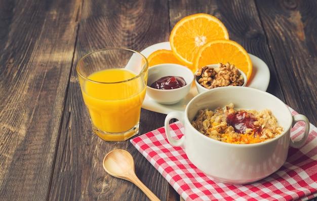 Płatki owsiane z orzechami włoskimi, skórką pomarańczową i dżemem na śniadanie na rustykalnym drewnianym tle
