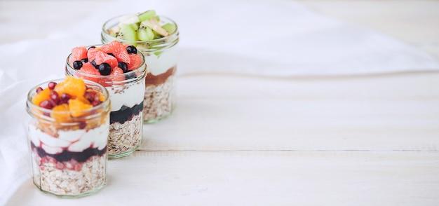 Płatki owsiane z owocami i płatkami w szklanym słoju