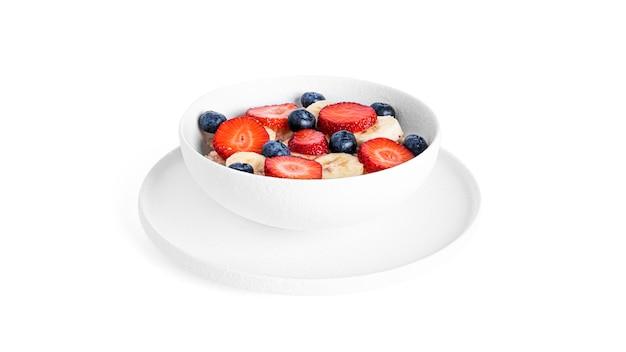 Płatki owsiane z owocami na białym tle. owsianka z truskawkami, jagodami i bananem.