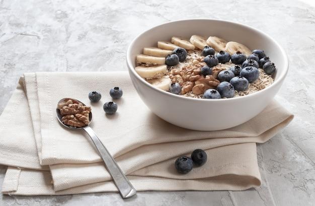 Płatki owsiane z pokrojonym bananem, jagodami i orzechami włoskimi na lnianym ręczniku na pyszne śniadanie