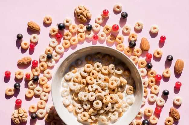 Płatki pełnoziarniste z jagodami i mlekiem na różowo. zdrowe, smaczne płatki śniadaniowe z jagodami, malinami i czerwoną porzeczką. wieloziarniste pełnoziarniste zdrowe płatki zbożowe ze świeżymi jagodami.