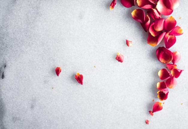 Płatki róż na marmurowym tle kwiatowy wystrój i wesele płaskie tło kartki z życzeniami dla...