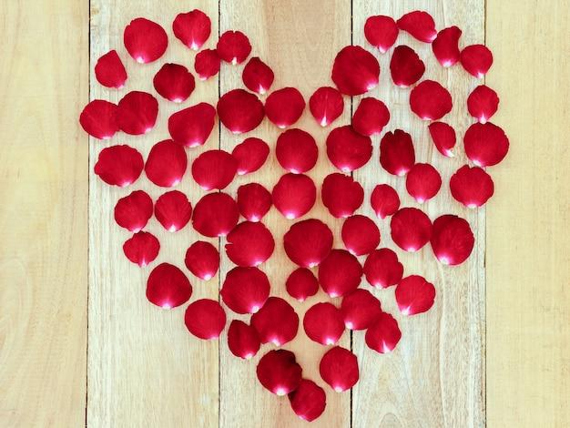 Płatki róż ułożone w kształcie serca na drewnianym tle.