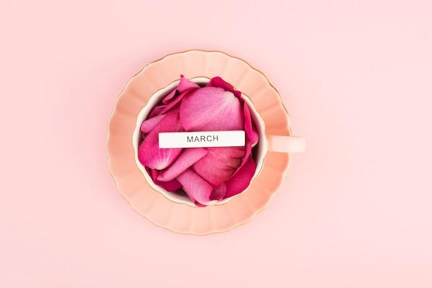 Płatki róż w filiżance herbaty na różowym stole, napis march