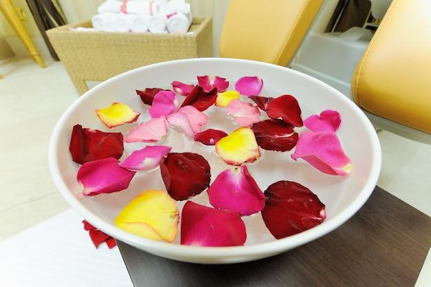 Płatki róż w naczyniu do pedicure. procedura spa
