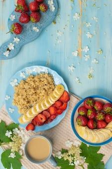 Płatki śniadaniowe z bananami i truskawkami filiżanka kawy widok z góry
