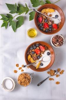 Płatki śniadaniowe z truskawkami i jogurtem na białym obrusie