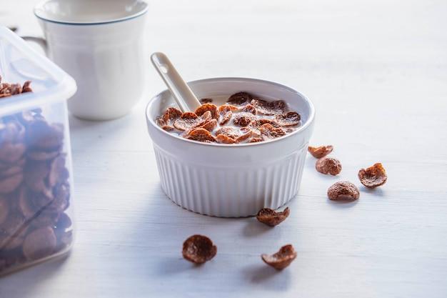 Płatki śniadaniowe ze świeżym mlekiem na białym stole