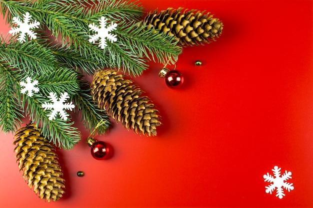 Płatki śniegu, gałęzie jodły i dekoracje świąteczne na czerwonym tle z miejscem na tekst. tło uroczysty nowy rok.