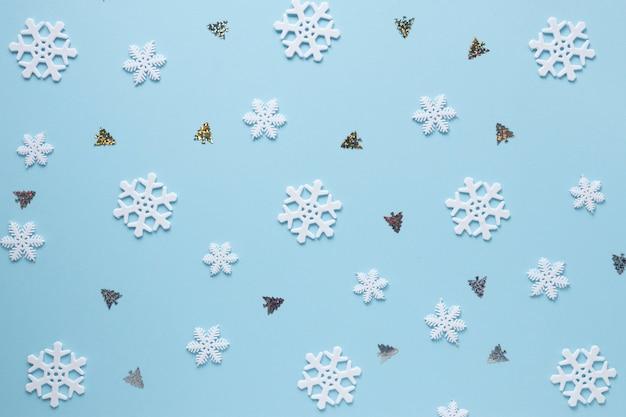 Płatki śniegu i choinki na błękitnym tle