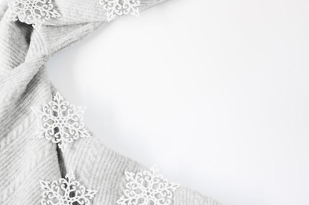 Płatki śniegu i szary sweter na białym tle