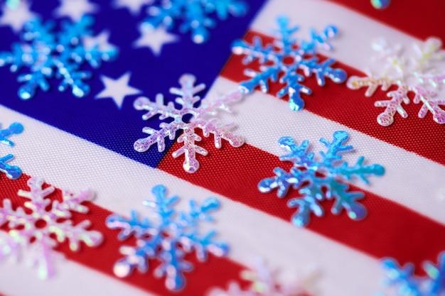 Płatki śniegu na flagę usa. amerykańska zima. prognoza pogody: opady śniegu lub burza śnieżna w stanach zjednoczonych.