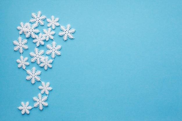 Płatki śniegu na niebieskim tle z miejscem na tekst.