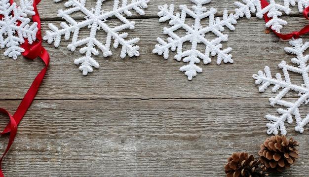 Płatki śniegu z szyszkami i czerwoną wstążką