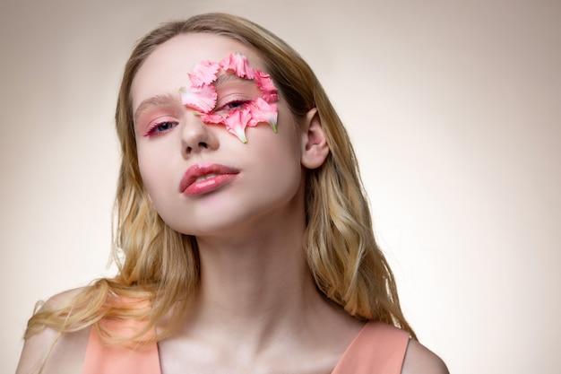 Płatki wokół oka. delikatna blond, atrakcyjna modelka z małymi różowymi płatkami wokół oczu