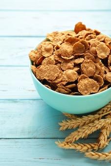 Płatki zbóż, kolce i ziarna żyta na niebieskim drewnianym stole. zdjęcie pionowe