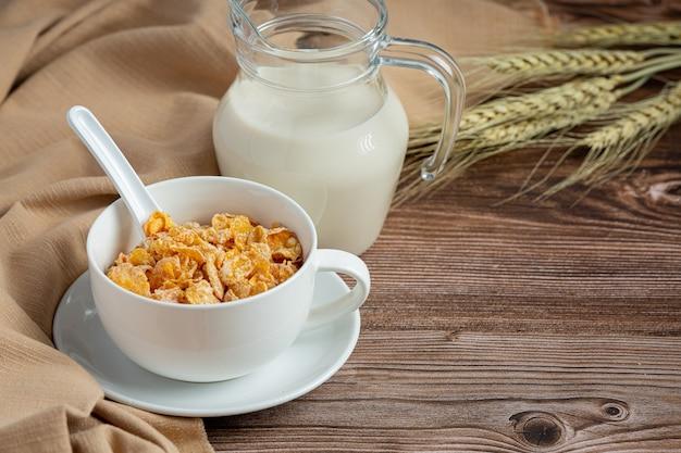 Płatki zbożowe w misce i mleku na ciemnym drewnianym tle