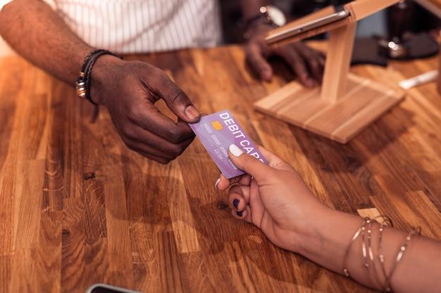 Płatność bezgotówkowa. widok z góry kobiecej ręki trzymanej w niej karty debetowej