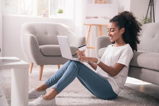 Płatność internetowa. przyjemna miła kobieta trzymająca laptopa i płacąca za rachunki przez internet