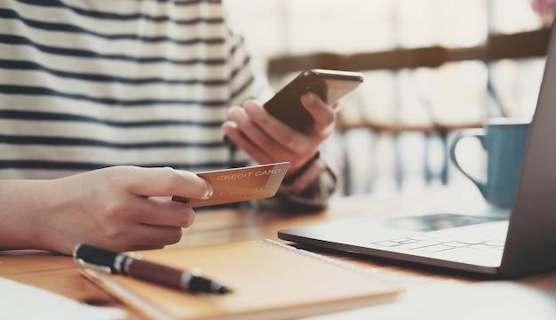Płatność online, kobiece ręce trzymając smartfon i za pomocą karty kredytowej na zakupy online. koncepcja cyberponiedziałku