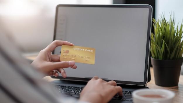 Płatność online, kobiece ręce trzymające kartę kredytową i używające laptopa do zakupów online z dźwiękiem vintage