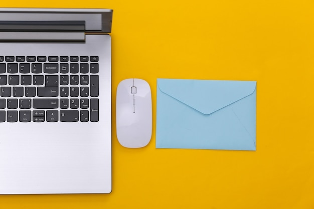 Płatność online. laptop z myszką pc, koperta na żółtym tle. widok z góry.
