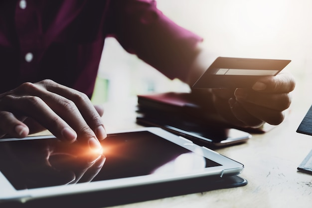 Płatność online, man's za pomocą cyfrowego tabletu i ręki trzymającej kartę kredytową do zakupów online. czarny piątek lub cyber poniedziałek koncepcja.