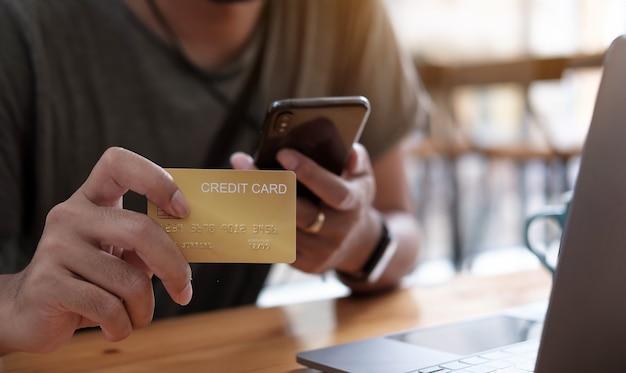 Płatność online, męskie ręce trzymając smartfon i za pomocą karty kredytowej do zakupów online. koncepcja cyberponiedziałku