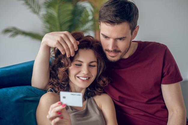 Płatność online. młoda para rozmawia o tym, co kupić w internecie