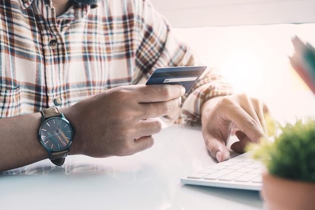 Płatność online, ręce mężczyzny trzyma kartę kredytową i korzysta z laptopa do robienia zakupów online