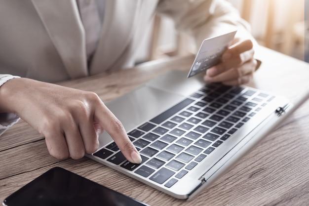 Płatność online, ręka młodego człowieka za pomocą laptopa komputerowego i ręka trzyma kartę kredytową na zakupy online.