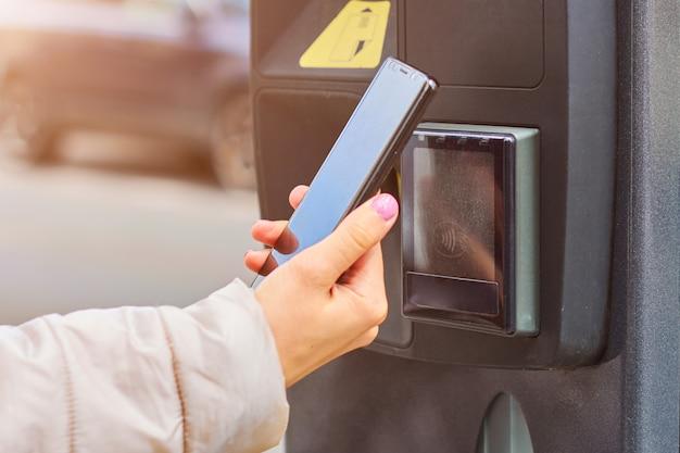 Płatność smartfonem z technologią nfc za parking publiczny z miejscem do kopiowania. koncepcja płatności zbliżeniowych.