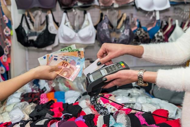 Płatność w sklepie z bielizną, karta z terminalem i euro