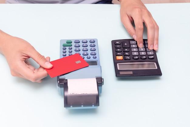 Płatność za zakupy kartą kredytową. trzymanie karty kredytowej nad kasą i obliczanie kosztu zakupu na kalkulatorze na niebieskim tle. koncepcja czarnego piątku