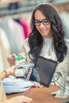 Płatność zbliżeniowa kartą kredytową przez młodą kobietę w centrum handlowym.