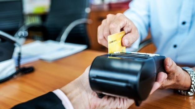 Płatności kartowe między biznesmenami za pośrednictwem urządzenia do obsługi kart kredytowych w biurze.