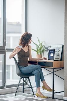 Płatności okresowe. ładna kobieta trzyma kartę kredytową i planuje dokonać płatności online